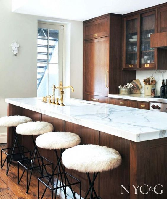 Dark wood kitchen with white marble countertop and white stools: