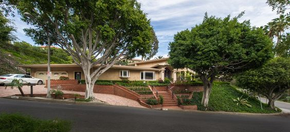 Traditional estate in Beverly Hills offers grand amenities and great views of Century City and Downtown LA.