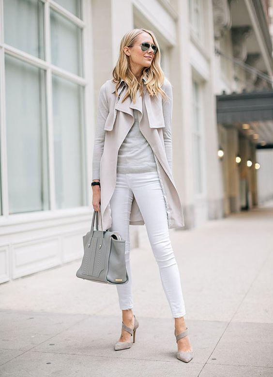 Mulher loira posa para foto de street style usando look claro de blusa de manga longa cinza, colete nude, calça skinny branca, scarpin nude e bolsa cinza