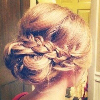 Interesting twist on the low, loose chignon! Instead of flowers or pins, this style is enhanced by adding a loose braid over the chignon. Crown is backcombed and smoothed for volume, with a few pieces around the face pulled loose to soften the look.