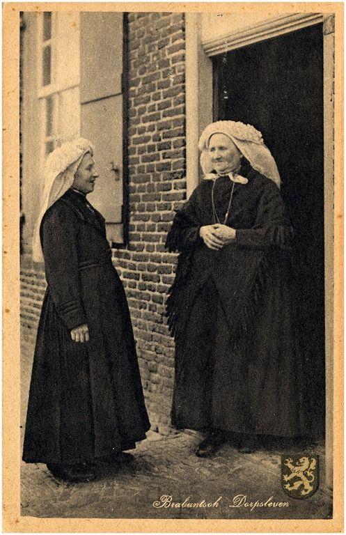 Twee vrouwen met poffers, de ene met een overjas, de andere met een schouderdoek, pratende bij een open deur 1923
