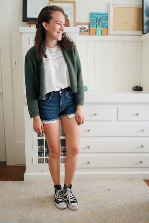woman in jean shorts, black Converse, white top with lacy detail on top, green cardigan
