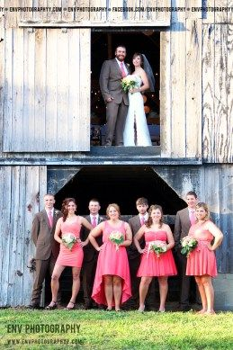 bride and groom with wedding party in old rustic barn