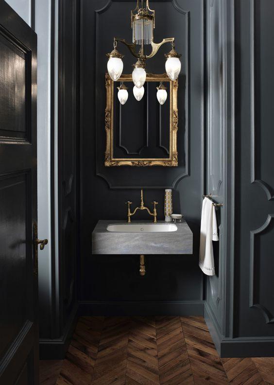Beautiful wood herringbone floors, dark wallls, floating vanity, vintage light and brass mirror.