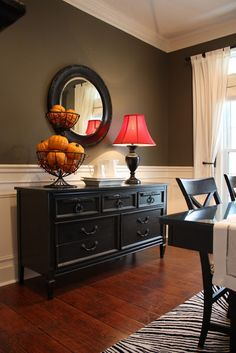 A black sideboard/ buffet table is a striking contrast to the dark color wall and white beadboard trim.  A round mirror, lamp with red shade and wire bowl are wonderful accessories.