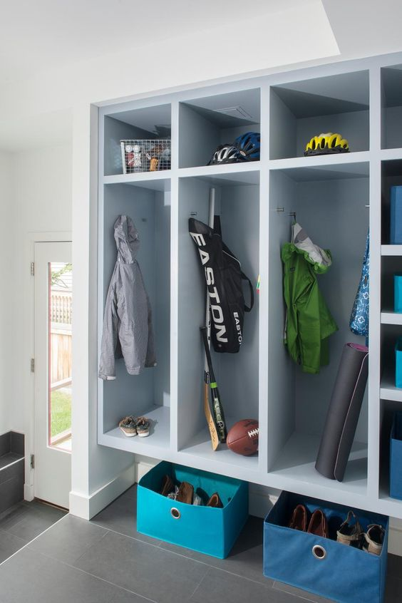 Tall, locker-style cabinets make storing sporting equipment and outerwear a breeze. Blue bins corral shoes and add a cheery pop of color.