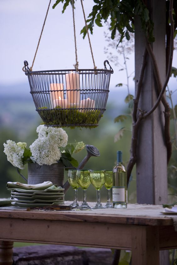I discovered clam baskets make a great hanging chandelier.   Hang with clothesline from a tree, beams or a pergola over your table. Pad the bottom with moss and stand pillar candles inside.