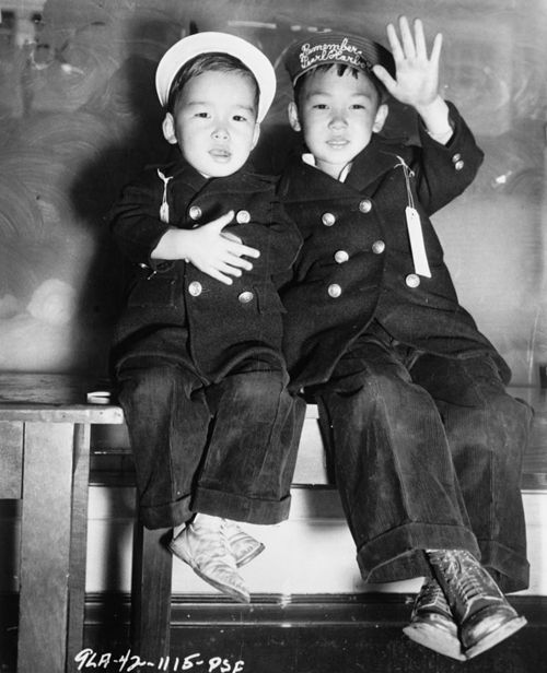 """Photo created by U.S. Army Signal Corps.  """"San Francisco: Two Japanese boys awaiting the bus that will take them to an internment camp.  One wears an embroidered hat that reads: Remember Pearl Harbor."""""""