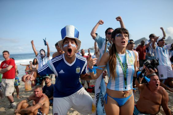 Photogenic fans of the World Cup - Day 10 - Argentine soccer team fans react to their team scoring against the Iran team as they watch on the screen setup at the Word Cup FIFA Fan Fest during on Copacabana beach June 21, 2014 in Rio de Janeiro, Brazil. Argentina won the match 1-0. (Photo by Joe Raedle/Getty Images)
