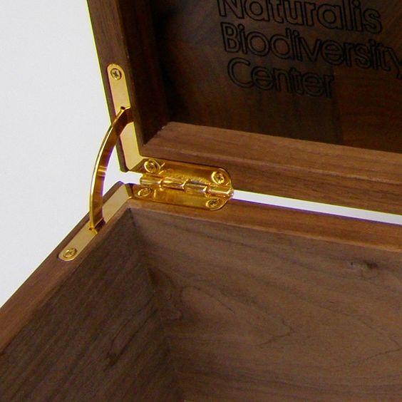 Massief notenhouten kist met klepdeksel op maat gemaakt met ingefreesde inscriptie. Deksle heeft door de messing Quadrant scharnier een begrenzing op 110 gr. DE klep blijft staan om je mooie producten te tonen.