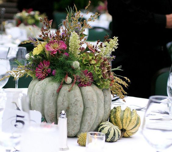 Simple but elegant centerpiece for fall with pumpkin and seasonal flowers/foliage