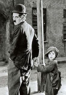Photographie de Charlot l'air énervé tenant la main à un petit garçon en haillons: