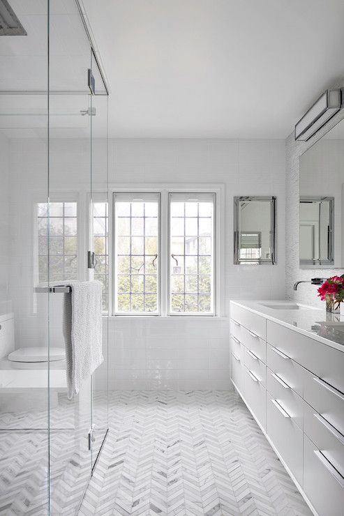 Sleek modern vanity, chevron marble floors, shower