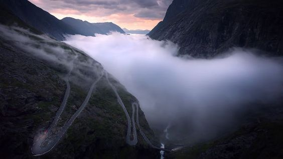 Andalsnes, Norway  The mountain road, Trollstigen, in western Norway.The late summer midnight sun seting as the fog sways through the valley below.