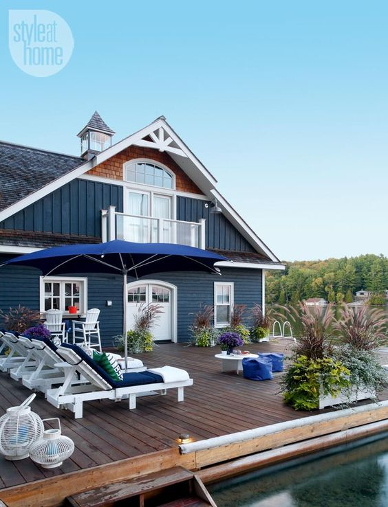 Facade de maison en bardage bleu donnant sur une terrasse en bois en bord  de l