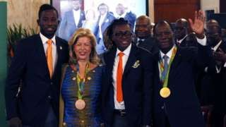 Image copyright                  EPA Image caption                                      Ivorian President Alassane Ouattara (R) and his wife Dominique Ouattara pose with the Olympians.                                Ivory Coast's two medallists from the Rio Olympic games have been given cash awards and houses by the president.  Cheick Cisse, who won taekwondo gold, was given $85,000 (£64,000) and Ruth Gbagbi, who won bronze in the women