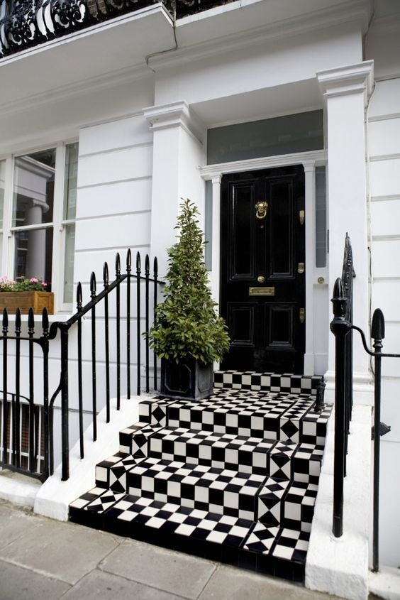Standing over a vibrant checker patterned set of steps, this black door features a plethora of subtle brass hardware, framed in smoked glass.: