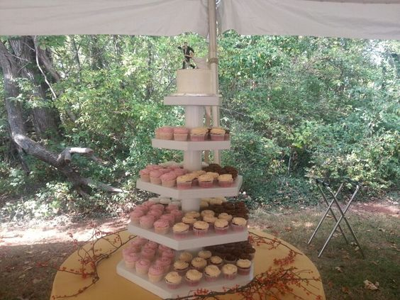 Cupcake display with small layer cake and topper for the bride to cut