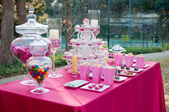 Cute set up with, the pink popcorn, cake pops, glasses with pink candy, and the chandelier looking cake holder!!