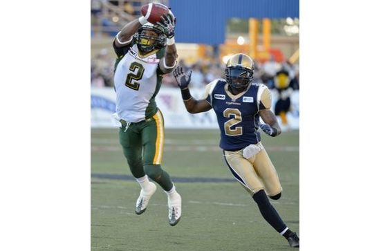 Edmonton Eskimos' Fred Stamps, left, makes a catch as Winnipeg Blue Bombers' Jovon Johnson defends during the first half of their CFL game in Winnipeg, July 26, 2012.