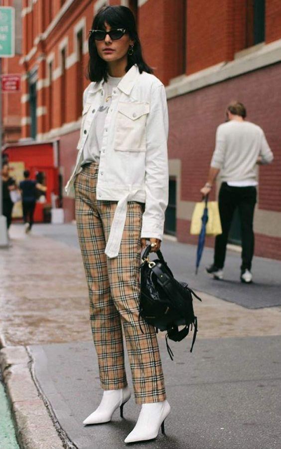 10 looks nada boring com alfaiataria. T-shirt branca, jaqueta branca, calça de alfaiataria listrada, bota, ankle boot branca