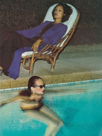 """Grace Coddington by Helmut Newton, Oct 1973, Vogue UK. """"On set in the South of France, Helmut Newton declares the eveningwear shoot """"bloody boring!"""" and calls for """"something sexy.""""[24] Editor Coddington obliges, lounging poolside in a black bandeau-top bikini, cat-eye sunglasses, and chunky pink Yves Saint Laurent heels."""""""