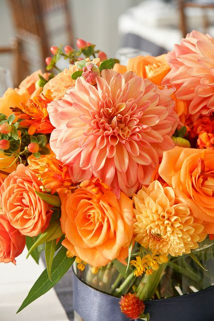 Gorgeous! Peach and orange dahlias, orange roses, and tangerine hypericum berries, perfect for a summer or fall wedding!