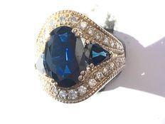 Anel em ouro branco de 18 kt, 10,93 g, com safira azul marinho natural de 4,6 ct, duas safiras azul marinho naturais, lapidação em pera, 1,6 ct no total (2x0,8) e diamantes lapidados em brilhante de aproximadamente 0,8 ct.