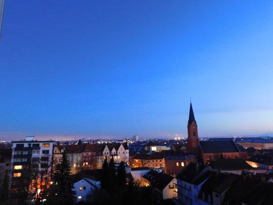 Unter der immer heller werdenden blauen Farbe des Himmels leuchten die Lichter in den Wohnungen eins nach dem anderen auf. Irgendwo strebt eine Kirche mit ihrem Turm zum Himmel. Die Energie des Neuanfangs ist jeden Morgen frisch und neu zu spüren.