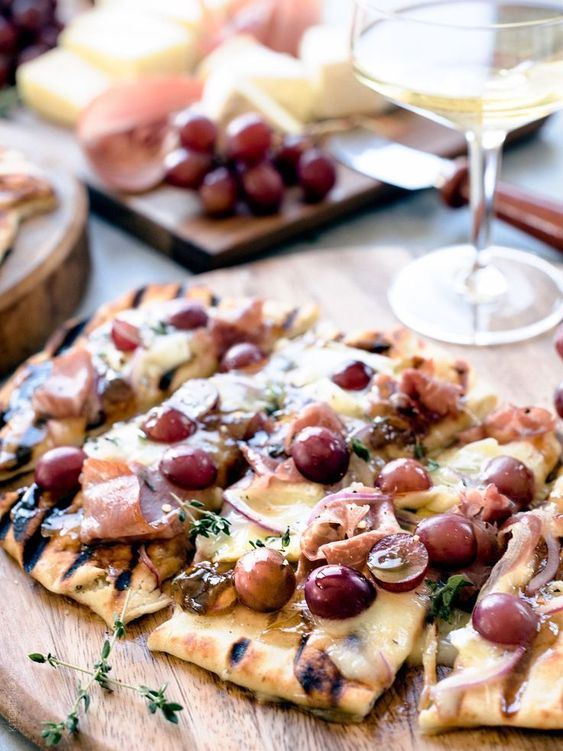 Grilled Naan Flatbread with Grapes, Onion Jam, Prosciutto and Double-Crème Cheese -- If you love melty cheese - and who doesn't!? - you'll love pairing these grilled flatbreads that celebrate the end of summer with juicy grapes, crispy prosciutto and a sweet and savory onion jam! Pair it with a glass of chardonnay and  #SavortheSummer with @CastelloUSA #ad