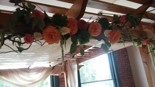 Coral flowers with curly willow to decorate the ceremony arbor
