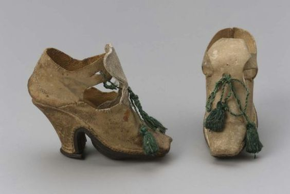 Pair of children's shoes, Italy, 1700,White sueded kid uppers; closed side and back seams; latchets tie behind and through high heart-shaped tongues with green tasseled silk cord. Square toed. Dark brown leather soles. White sueded kid-covered Louis heels, top pieces. White kid insoles.