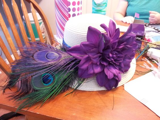 I made a fancy hat for the Belmont Stakes race!  A couple of peacock feathers, a fluffy black feather, a massive purple flower, and a trim made of wide royal blue ribbon, deep purple lace, and thinner lemongrass green ribbon.  I ADORE it!