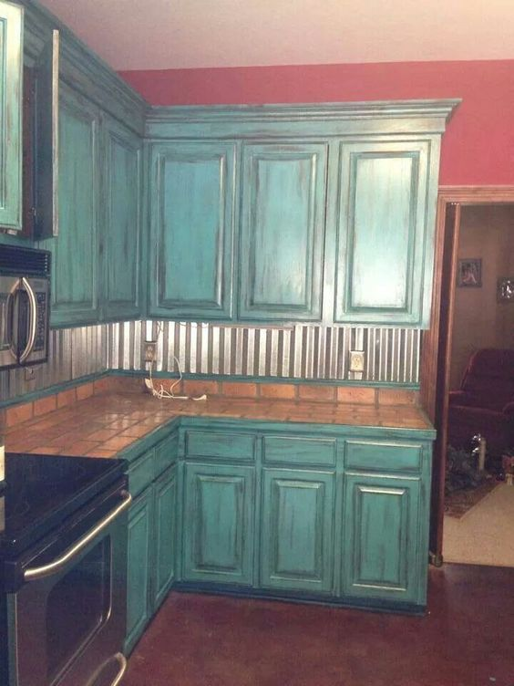 Corrugated metal backsplash & distressed teal cabinets See more at http://www.fashionisly.com
