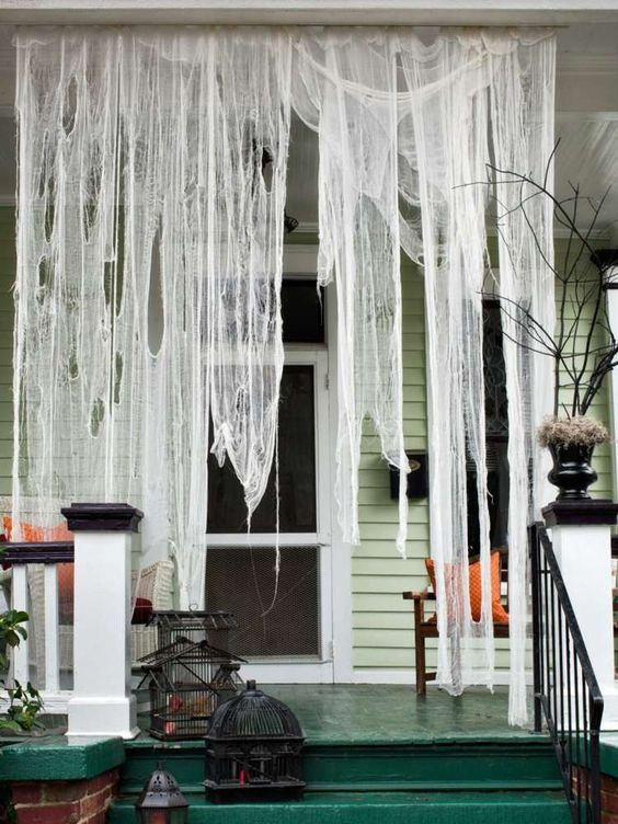 Use cheesecloth to decorate your door for Halloween to make it look like it's covered in hanging cobwebs.