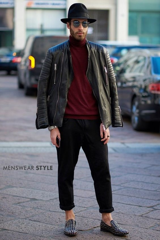 This elegantly stylish guy wears black fedora hat, burgundy roll neck, black leather jacket and studded loafers on the streets of Milan.
