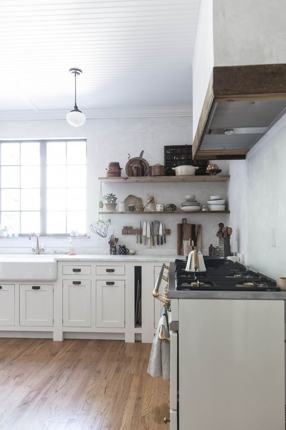 See more of this stunning farmhouse kitchen! Beth Kirby's modern farmhouse style kitchen decor with its rustic shelves, elegant Lacanche Sully range, and apron front farm sink. #whitekitchen #kitchenideas #modernfarmhouse #farmhousekitchen #bethkirby #rusticdecor #kitchendecor