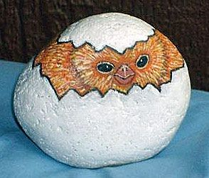 Painted rock chick peeping from an egg: