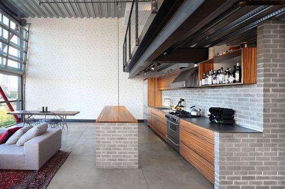 Loft americano in stile industriale - La cucina è stata completamente ridisegnata sulle esigenze della giovane coppia, modulando gli spazi lavoro tra un banco a isola e un grande elemento a parete, entrambi in mattoni. Sullo sfondo la parete è decorata con una carta da parati del designer Brian Paquette ispirata ai pattern giapponesi.