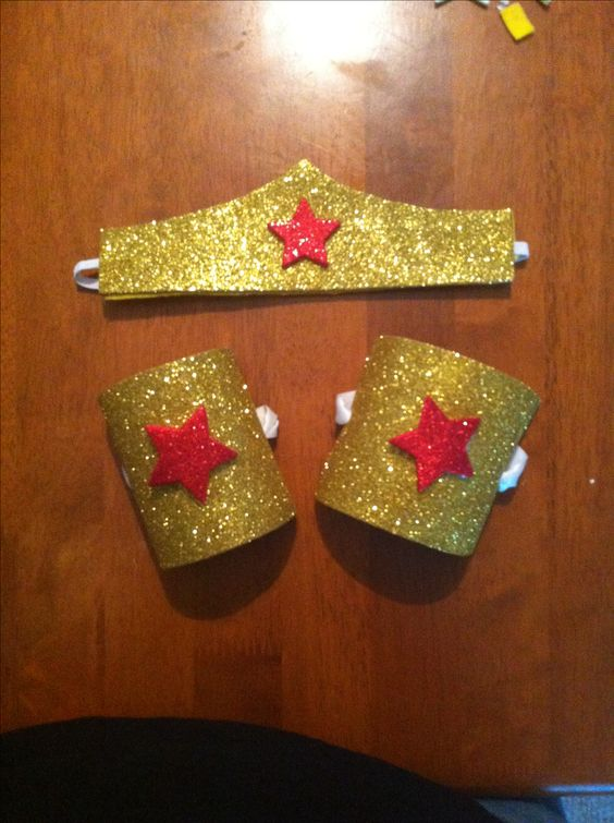 DIY Wonder Woman tiara and bracelets. Tiara: found a template on Pinterest for the shape of the crown. Then traced it onto peel &stick glitter foam sheet. I took a piece of elastic and hot glued it in between the glitter foam and felt. Bracelets, two toilet paper rolls cut for openings then cut and glued glitter foam sheets to them. Stars are peel and stick glitter foam also. So easy, so cheap!