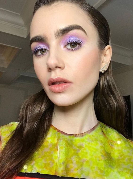 Lily Collins purple eyeshadow makeup look and slicked back hair style