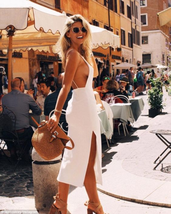 Braless beauty: Natasha Oakley (pictured) swapped her bikini-clad style for a silk white dress as she flaunted plenty of sideboob during a sunny trip to Rome, Italy on Thursday:
