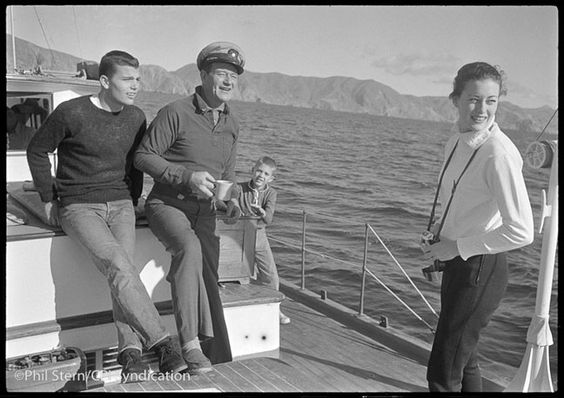 """On his yacht off the coast of Marina del Rey in the 1950s, Wayne is joined by his son Patrick (left) and daughter Toni, two of the four children he had with his first wife, Josephine. The boy in the middle is Stern's son, Philip, who grew up to become a pilot and was killed in a crash in the early '60s. """"This one is a little painful to look at,"""" Stern says."""