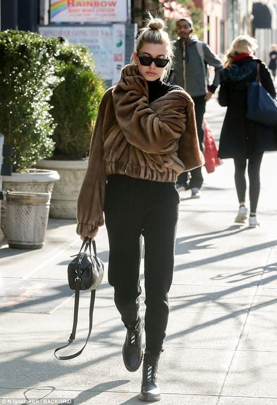 Real or faux? Hailey Baldwin bundled up in a brown fur hooded jacket while strolling through Manhattan on Tuesday