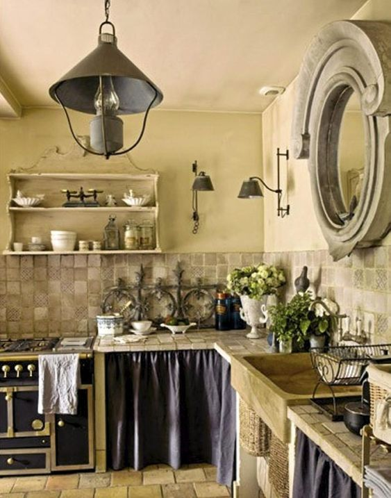 French country kitchen with skirted lower cabinets and dramatic mirror above stone backsplash. #french #kitchen #farmhouse #europeancountry #rusticdecor