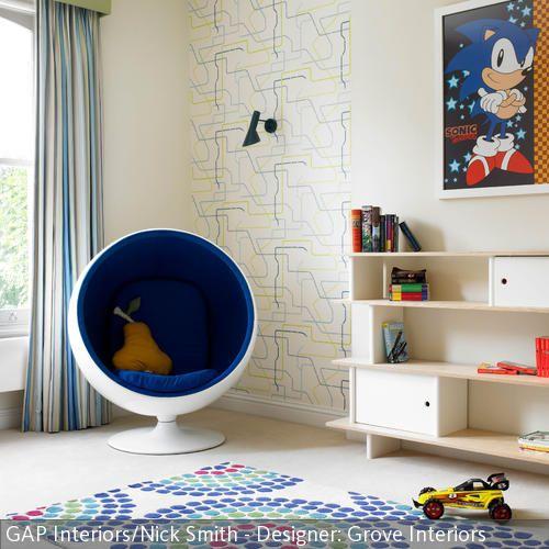 Der Hingucker des Kinderzimmers ist der Schalensessel mit blauer Fütterung. Zusammen mit dem gepunkteten Teppich in Blau, Rot und Grün und der Wandtapete mit  …