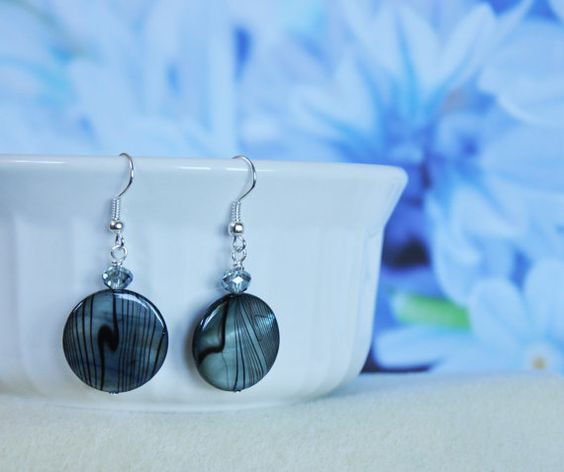 These beautiful lentil shell beads create their own personal designs that make these earrings so stunning. Black stripes over top of the blue shell allow the natural shine and depth from shell to add light and brightness to these earrings.  Very light yet strong, fun to wear for a truly unique look or gift to give.  Dangle length is 1 **Please note that because these earrings are made of natural shell they may have slight imperfections on the backside of the earrings. **