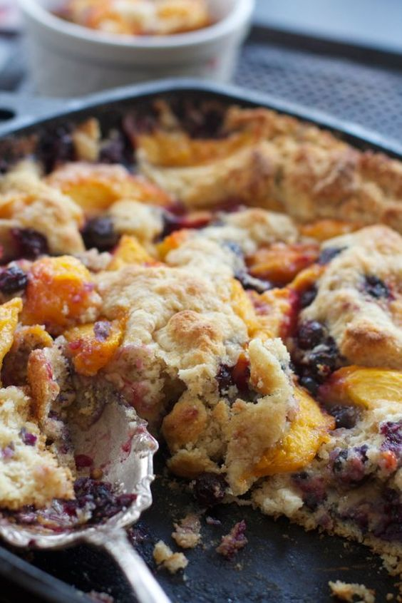 Southern Fresh Peach Cobbler made with buttermilk, & fruit on top, as the biscuit dough pushes its way to the top.