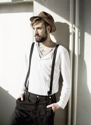 pants, braces, white v neck t-shirt, white short, hat, long fringe showing and beard.