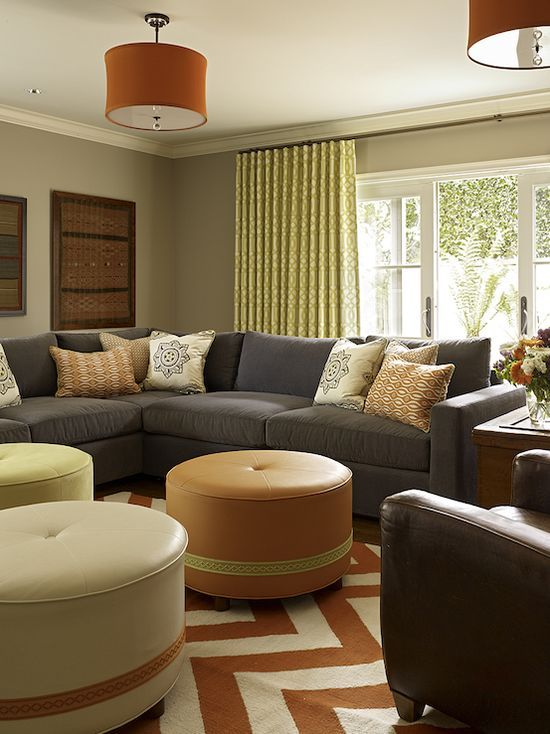 Contemporary living room design with blue modern sectional sofa, orange  zigzag chevron rug, white & orange round leather tufted ottomans, brown lea